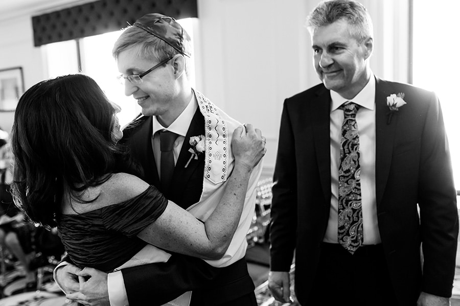 Groom hugs mother as dad looks on after they walked him down the aisle for a Jewish ceremony.
