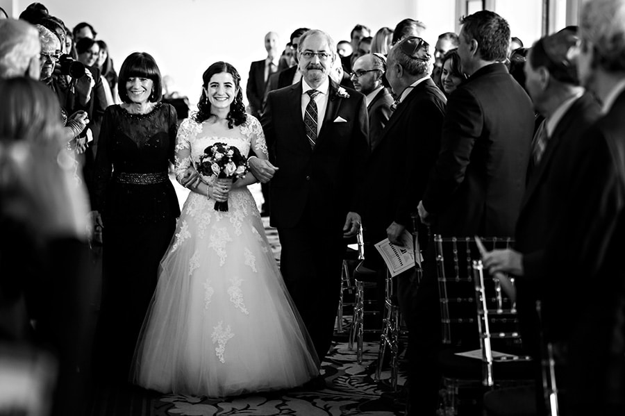 The bride and her parents walk down the aisle during a Jewish ceremony at The Downtown Club in Philadelphia, PA.