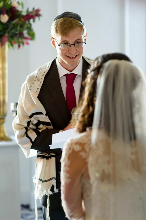 Groom looks at bride during his wedding vows.