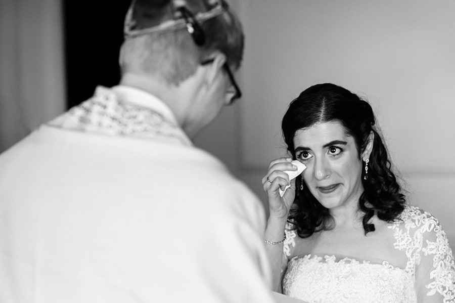 Bride wipes tears away as groom says his wedding vows in Jewish ceremony at the Downtown Club in Philadelphia.