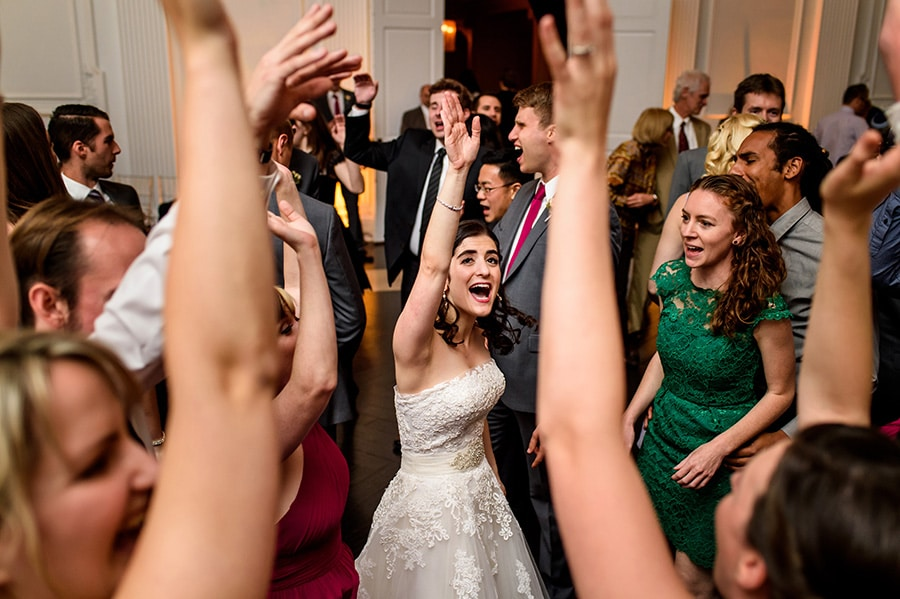 Bride dances in the center of wedding guests.
