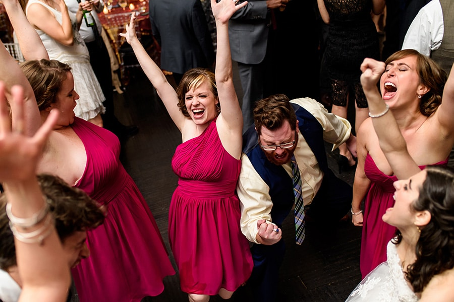 Bridesmaids and guests throw their hands up in the air as they dance during wedding reception.
