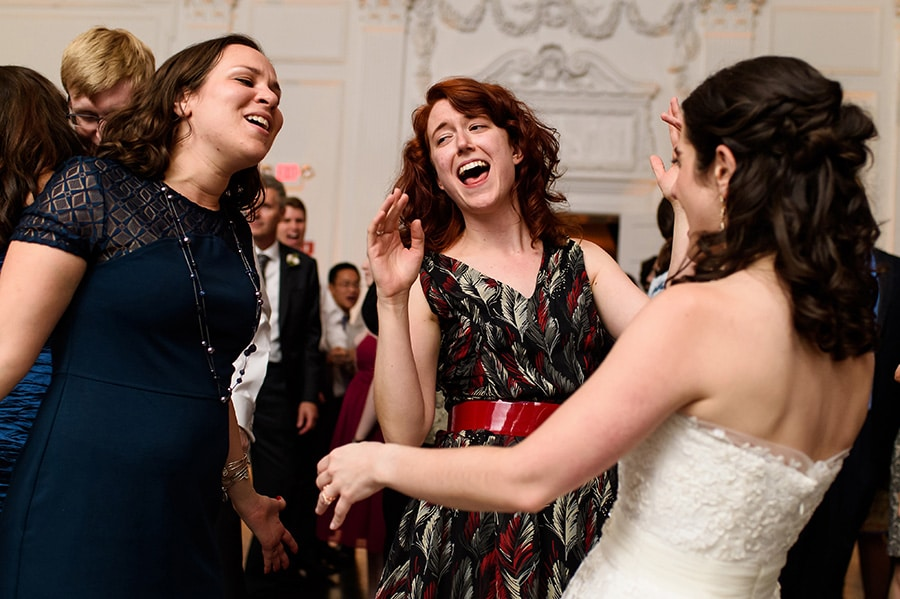 Bride and two wedding guests sing along to a song on the dance floor.