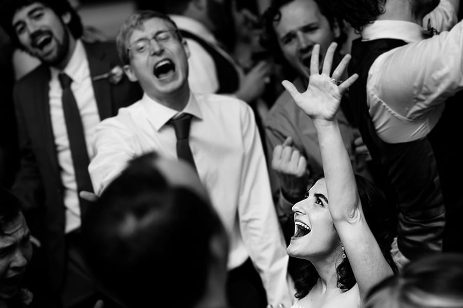 Bride throws her arm into the air during wedding reception.
