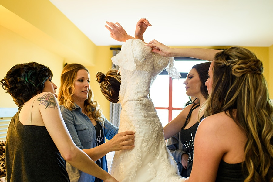 Bride awkwardly get into wedding dress with help from bridesmaids.