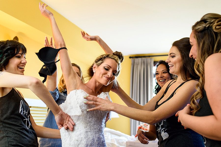 Bride awkwardly getting into her wedding dress with help from her bridesmaids.