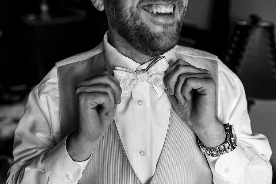 Close up of groom smiling while he puts his bowtie on.