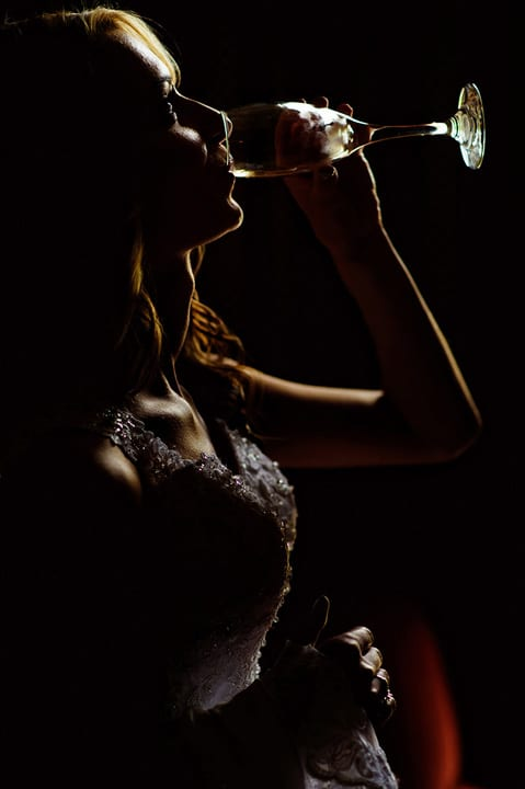 Moody image of a bride drinking from her champagne glass.