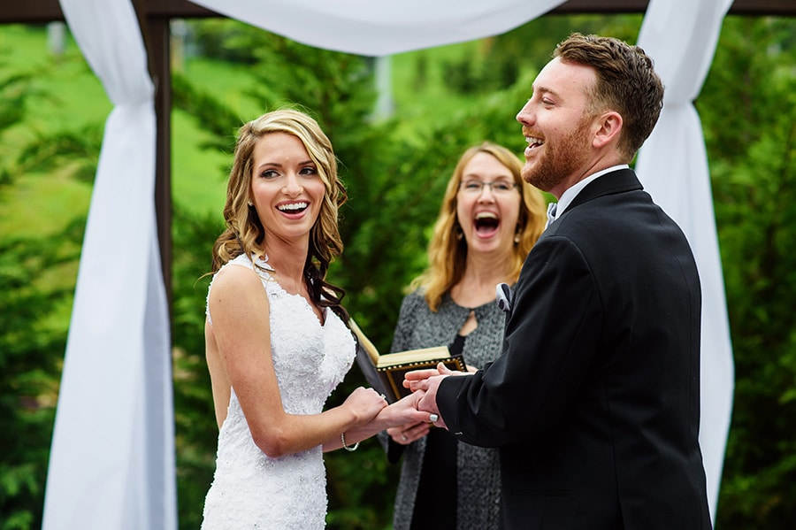 Bride, groom and officiant laugh during wedding ceremony at Bear Creek Mountain Resort.