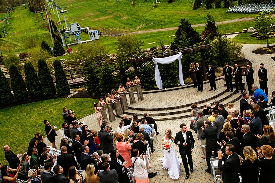 Bride and groom walk down aisle after wedding ceremony at Bear Creek Mountain Resort.,