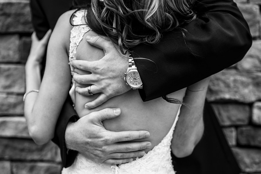 Groom's hands squeeze bride tightly.