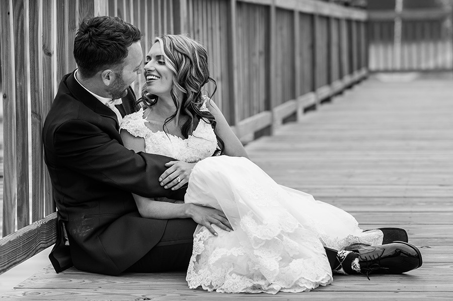 Bride and groom snuggle on dock.