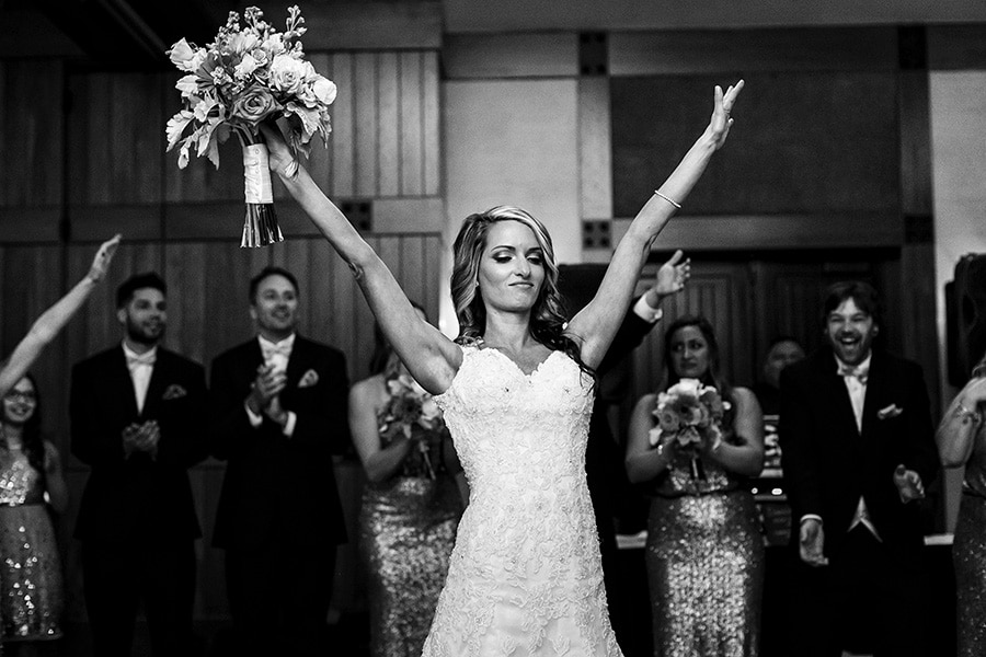 Excited bride throws her hands in the air as she enters reception at Bear Creek Mountain Resort.