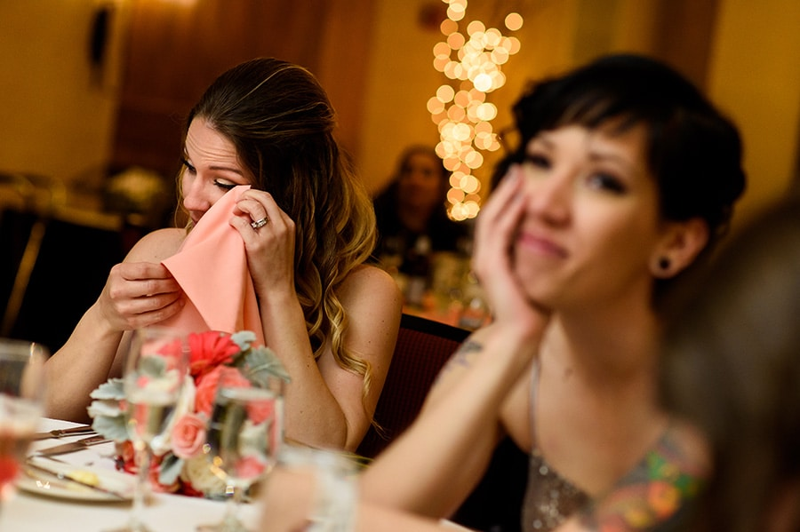 Wedding guests wipe tears away during wedding maid of honor speech.