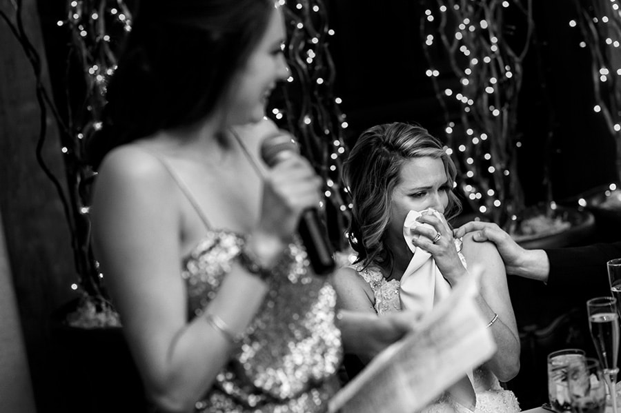 Bride wipes tears away during wedding toast by maid of honor.