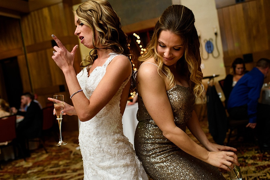 Bridesmaid and bride dance during wedding reception at Bear Creek.