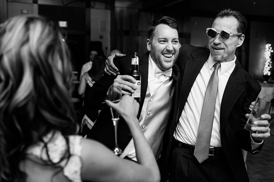 Wedding guest dances with his arm around the groom during wedding reception at Bear Creek in Macungie, PA.