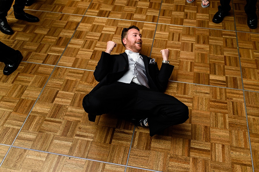 Groom dances on the floor during wedding reception.