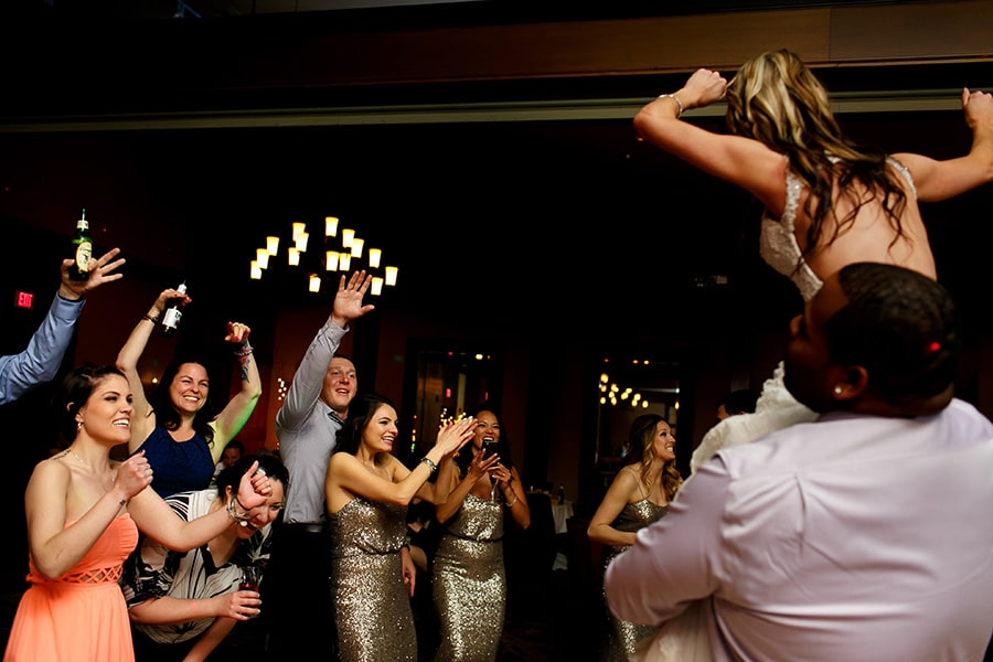 Wedding guests laugh and cheer as bride's friend lifts her on his shoulder during wedding reception at Bear Creek in Macungie, PA.