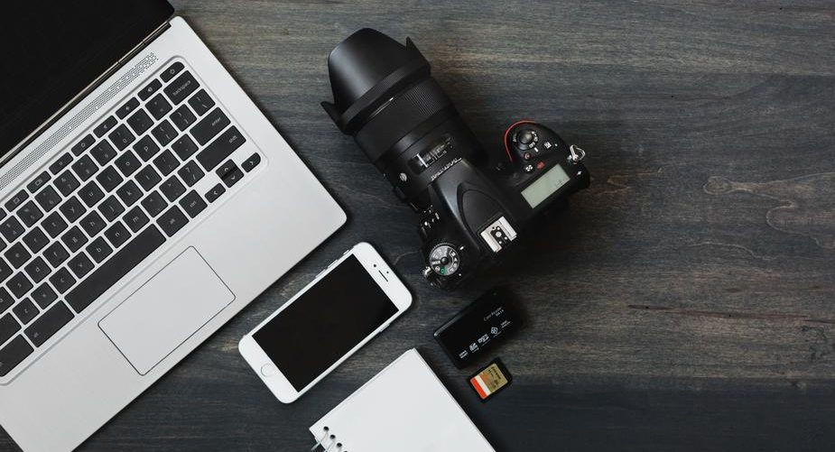 Photo of minimal photograph gear includes camera, phone, laptop and notepad at a photographer's desk.
